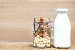 Eine Vielzahl von Nüssen in ein Flaschenglas und in ein Glas Milch auf Stockfoto