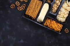 Eine Vielzahl von Snäcken auf dem Kasten für Bier auf einer konkreten schwarzen Tabelle Stockfoto
