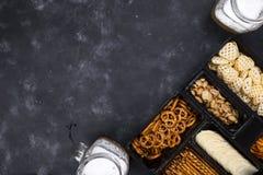 Eine Vielzahl von Snäcken auf dem Kasten für Bier auf einer konkreten schwarzen Tabelle Lizenzfreies Stockbild