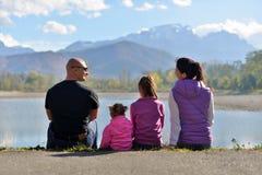Eine vierköpfige Familie sitzen nahe dem See auf dem Hintergrund von Bergen lizenzfreie stockfotografie