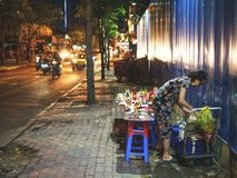 Eine vietnamesische Frau, die Produkte auf Straße verkauft lizenzfreie stockbilder