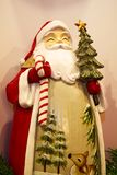 Eine Volkskunstfigürchen von Santa Claus einen Baum und eine Zuckerstange halten lizenzfreie stockfotografie