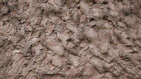Eine Wand des Schlammes, dekorativer Hintergrund des Zementkitts, eine Mischung von Erde geschmiert aus den Grund, ein Muster des Stockfoto