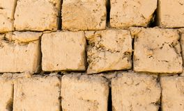 Eine Wand des Ziegelsteines des luftgetrockneten Ziegelsteines als Hintergrund Lizenzfreie Stockfotos