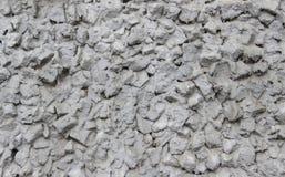 Eine Wand hergestellt vom zerquetschten Stein- und Schrottziegelstein vergipst mit Zement Lizenzfreies Stockbild