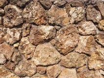 Eine Wand von Natursteinen von braunen Schatten mit roher, rauer Oberfläche Stockbilder