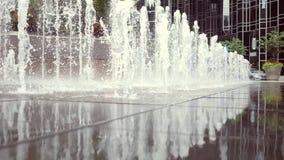 Eine Wasserfunktion nahe einem Geschäft oder Gesellschaft in der im Stadtzentrum gelegenen Stadt stock video footage