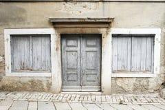 Eine Weatherbeaten Tür und Blendenverschlüsse Stockfoto