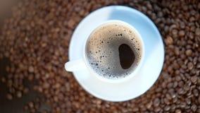 Eine weiße Kaffeetasse steht auf einem Stapel von Röstkaffeebohnen stock video