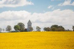 Eine weiße Kirche mit einem Feld des Rapssamens im Vordergrund Stockfotografie