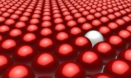Eine weiße Kugel innen unter vielen roten Kugeln Lizenzfreies Stockbild
