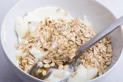 Eine weiße Platte halb voll mit Hafern mit Jogurt und Honig, mit a Lizenzfreie Stockbilder