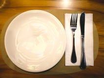 Eine weiße Platte mit silberner Gabel und Messer für das Essen der Pizza das Stockbilder