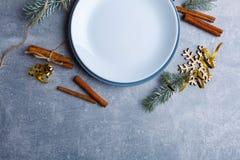 Eine weiße Platte und unter ihr blaue Platten, gezierte Zweige, Zimtstangen und Schneeflocken Ansicht von oben Stockbild