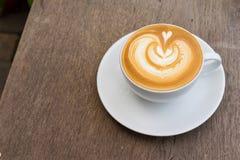 Eine weiße Tasse Kaffee Lattekunst auf hölzerner Tabelle Lizenzfreies Stockfoto