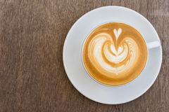 Eine weiße Tasse Kaffee Lattekunst auf hölzerner Tabelle Stockfotos