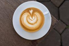 Eine weiße Tasse Kaffee Lattekunst auf hölzerner Tabelle Lizenzfreies Stockbild