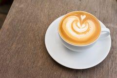 Eine weiße Tasse Kaffee Lattekunst auf hölzerner Tabelle Stockfotografie