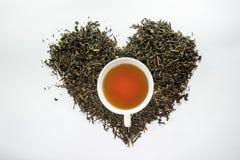 Eine weiße Tasse Tee auf dem getrockneten Teeblatt in der Herzform Lizenzfreies Stockfoto
