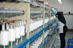 Eine weibliche Arbeitskraft, die in der Textilwerkstatt arbeitet Stockfotos