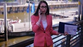 Eine weibliche Exekutive wird durch einen Vertrag vergangen und eine Debatte mit den Partnern am Telefon hat stock video