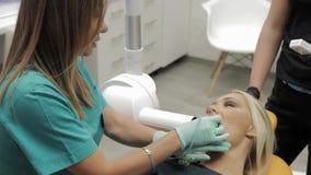 Eine weibliche Gesamtlänge eines Zahnarztes, der einen Röntgenstrahl von einem Patienten teethin hijab vorschlägt ihren Patienten stock footage