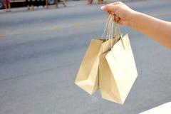 Eine weibliche Hand, die braune Taschen mit Pflasterungshintergrund hält lizenzfreies stockfoto