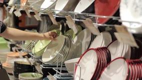 Eine weibliche Hand an einem Supermarkt wählt Platten stock video footage