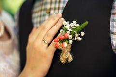 Eine weibliche Hand mit einem Verlobungsring befestigt ein butanier zur Bräutigam ` s Klage lizenzfreies stockfoto