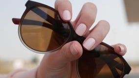 Eine weibliche Hand mit einer schönen Maniküre hält Sonnenbrille-, Mode- und Schönheitshandpflegekonzept stockfotos