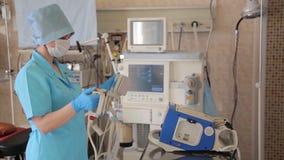 Eine weibliche Krankenschwester bereitet einen Defibrillator für eine chirurgische Operation vor Neue medizinische Technologien 4 stock footage