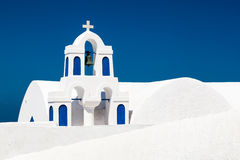 Eine weiße Kirche mit blauen Elementen in Oia auf Santorini-Insel, Griechenland Stockbilder