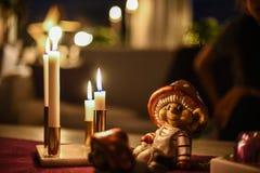 Eine Weihnachtsfigürchen, die auf einer Tabelle nahe bei brennenden Kerzen sitzt Lizenzfreies Stockbild