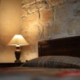 Eine Weinleselampe neben einem Bett Stockbild