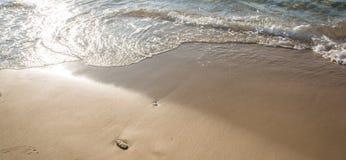 Eine Welle, die einen sandigen Strand streichelt Lizenzfreie Stockfotos