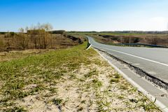 Eine wickelnde Landstraße, die in den Abstand gegen den Hintergrund einer schönen Frühlingslandschaft, Felder, Wiesen, Wälder aus stockbilder