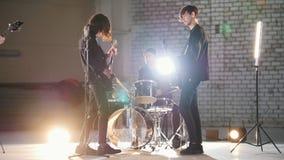 Eine Wiederholung Eine junge Gruppe von Personen, die Rockmusik in helle Lichter spielt stock video