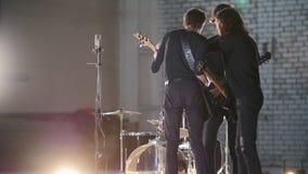 Eine Wiederholung Eine junge Gruppe von Personen, die Rockmusik spielt und sie bespricht stock footage