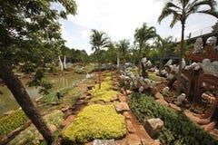 Eine Wiese mit Eule und Gras und Bäume und Steine und Teich im tropischen botanischen Garten Nong Nooch nahe Pattaya-Stadt in Tha Lizenzfreie Stockfotografie
