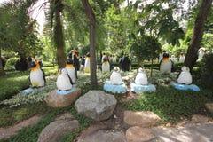 Eine Wiese mit Pinguinen und Gras und Bäume und Steine im tropischen botanischen Garten Nong Nooch nahe Pattaya-Stadt in Thailand Lizenzfreies Stockbild