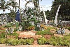 Eine Wiese mit Waschbären und Gras und Bäume und Steine im tropischen botanischen Garten Nong Nooch nahe Pattaya-Stadt in Thailan Stockfotografie