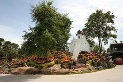 Eine Wiese mit Waschbären und Gras und Bäume und Steine im tropischen botanischen Garten Nong Nooch nahe Pattaya-Stadt in Thailan Lizenzfreies Stockfoto