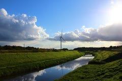 Eine Windkraftanlage in einer ruhigen Landschaft mit grünem Gras, blaue SK Lizenzfreie Stockbilder