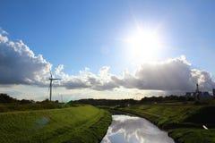 Eine Windkraftanlage in einer ruhigen Landschaft mit grünem Gras, blaue SK Lizenzfreie Stockfotos