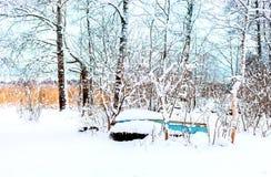 Eine Winterlandschaft mit dem alten verlassenen Boot auf dem Ufer Lizenzfreies Stockfoto