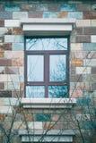 Eine Winterszene des Fensters auf Ziegelsteinwand und -baum branchs Stockfotos