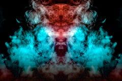 Eine Wolke des dynamischen Rauches ausgeatmet von einem vape wird in den verschiedenen Farben und im Zerstreuen in Form des Kopfe lizenzfreies stockfoto