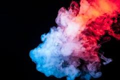 Eine Wolke des lokalisierten farbigen Rauches ausgeatmet von einem vape: blau, rot, Orange, rosa; auf einem dunklen Hintergrund stockfotografie