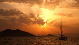 Eine Yacht in dem Meer während eines Sonnenuntergangs Stockfotografie