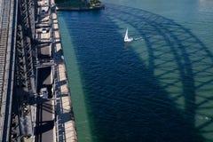 Eine Yacht segelt unter Sydney Harbour Bridge Lizenzfreie Stockbilder